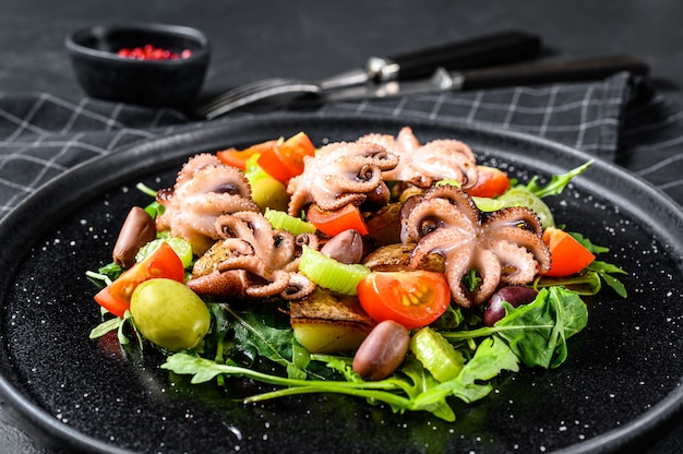 Warme salade met octopus, aardappelen, rucola, tomaten en olijven. zwarte achtergrond. bovenaanzicht