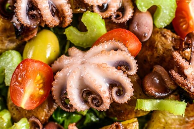 Warme salade met octopus, aardappelen, rucola, tomaten en olijven.