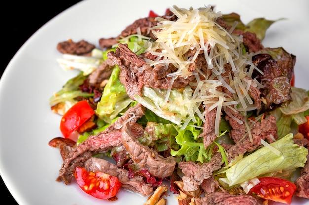 Warme salade met vlees en kaas op een witte plaat