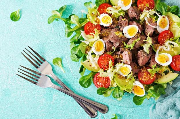 Warme salade van kippenlever, avocado, tomaat en kwarteleitjes. gezond eten. dieet menu. plat leggen. bovenaanzicht