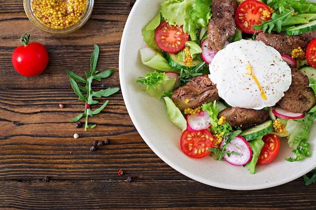 Warme salade van kippenlever, radijs, komkommer, tomaat en gepocheerd ei. gezond eten. dieet menu. bovenaanzicht plat leggen.