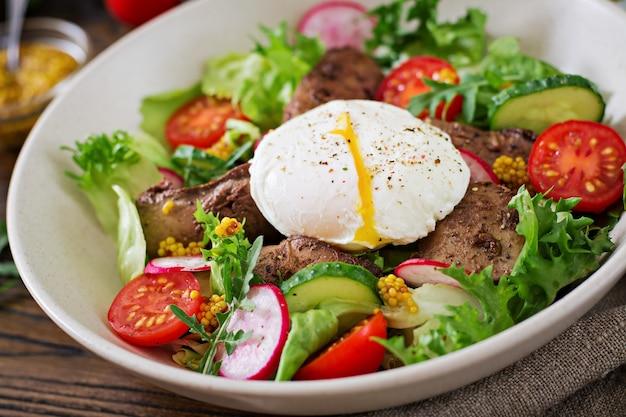 Warme salade van kippenlever, radijs, komkommer, tomaat en gepocheerd ei. gezond eten. dieet menu
