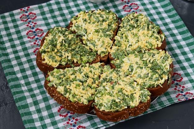 Warme sandwiches met daslook, bosuitjes, eieren, kaas en peterselie