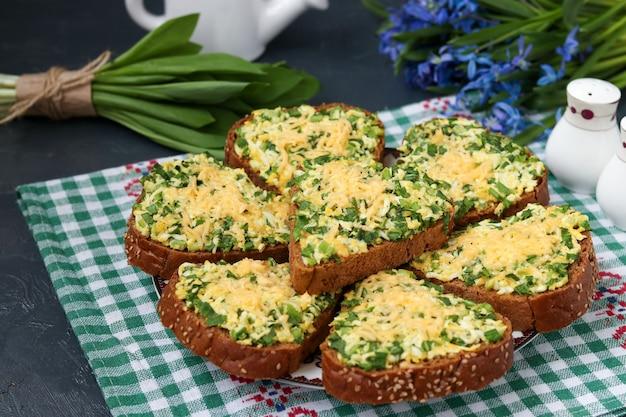 Warme sandwiches met groene uien, daslook, eieren, kaas en peterselie
