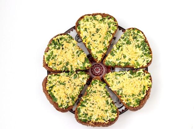 Warme sandwiches met wilde knoflook, groene uien, eieren, kaas en peterselie gelegen op een witte ondergrond, bovenaanzicht