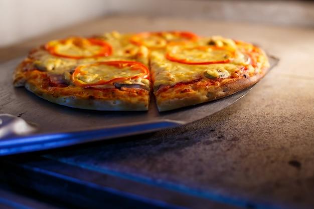 Warme smakelijke amerikaanse pizza met tomatenkaas en vlees met een dikke korst op een metalen schop, de bakker haalt de pizza uit de oven