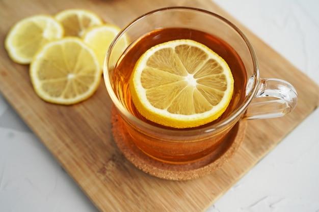 Warme thee met citroen op een houten bord. een warm drankje voor verkoudheid. de helende eigenschappen van citroen