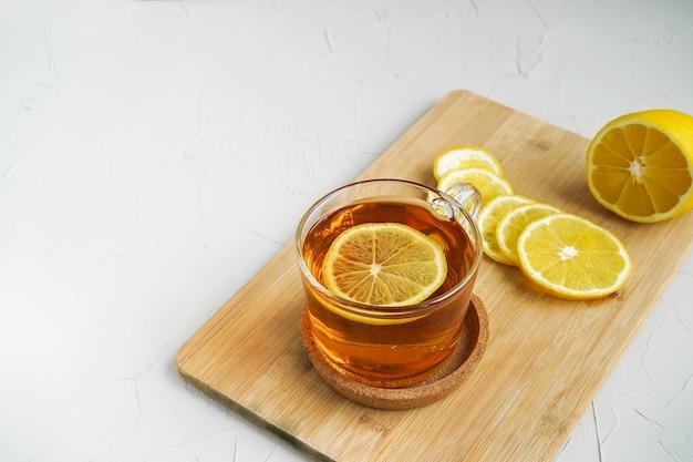 Warme thee met citroen op een houten bord. een warm drankje voor verkoudheid.