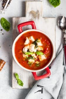 Warme tomatensoep met kip, groenten en basilicum.