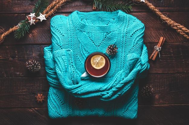 Warme trui, dennenappels, een mok hete thee met citroen, kaneel en anijssterren. winterkleren en drankjes. winter concept.