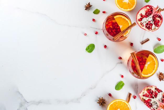 Warme verfrissende cocktail met granaatappel, sinaasappels, kaneel, kruiden en munt