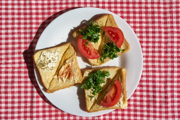 Warme verse toast met kaas en tomaat op een plaat, vlakke weergave