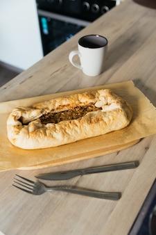 Warme versgebakken appeltaart en kopje koffie thuis in de keuken