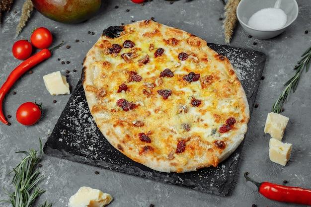 Warme vier kazen heerlijke rustieke zelfgemaakte amerikaanse pizza met dikke korst op zwarte tafel.