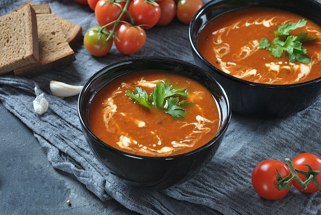 Warme wintersoep. roodgloeiende tomatensoep met knoflook, zoete paprika, peterselie, geserveerd met room en zuurdesembrood in twee zwarte keramiek kommen op een grijze achtergrond