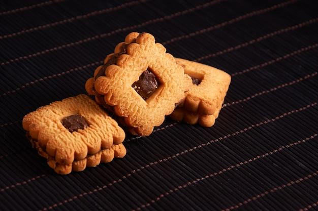 Warme zelfgemaakte gingersnap koekjes gegarneerd met chocolade op rode stijlachtergrond