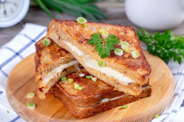 Warme zelfgemaakte sandwich met mozzarellakaas op een houten tafel
