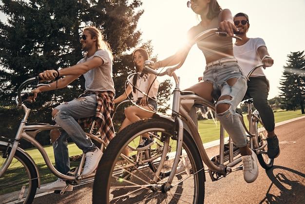 Warme zon en een geweldig gezelschap. groep gelukkige jonge mensen in vrijetijdskleding die lacht terwijl ze samen buiten fietsen