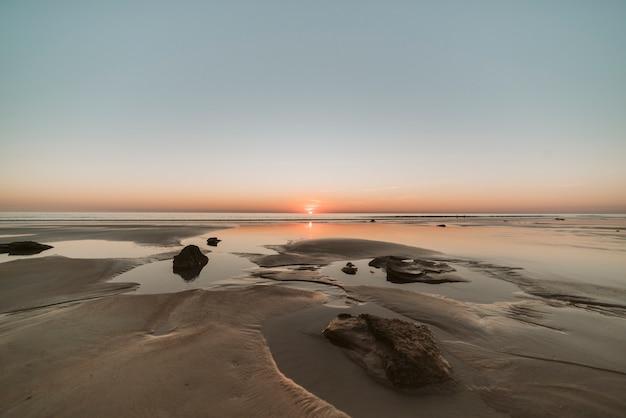 Warme zonsondergang in een uitstekend en beroemd australisch strand, bekend door zijn verbazingwekkende kleuren terwijl de zon ondergaat.
