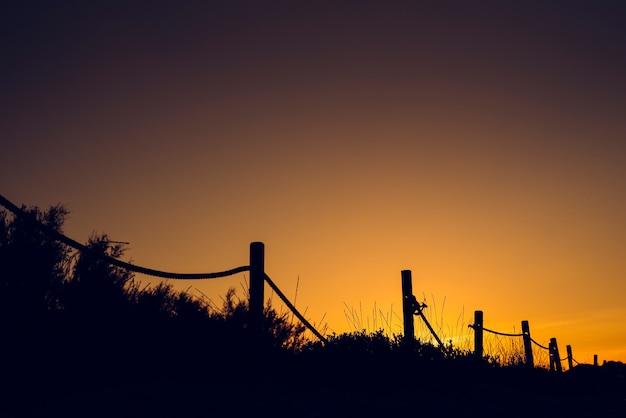 Warme zonsondergang met silhouet van strandduinen