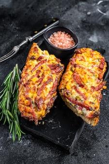 Warmgebakken open baguettesandwich met ham, bacon, groenten en kaas. zwarte achtergrond. bovenaanzicht.