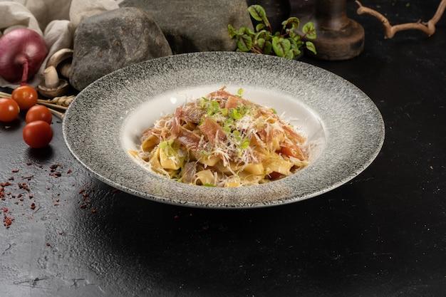 Warmgekookte tagliatelle pasta met parmaham, parmezaanse kaas en kruiden