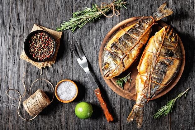 Warmgerookte zeebrasem, orata, dorado-vis op een houten ronde snijplank op een donkere houten tafel met een vork, rozemarijn en peperkorrel, horizontaal uitzicht van bovenaf, plat gelegd, vrije ruimte