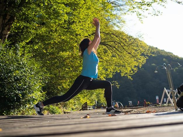 Warming-up doen in de open lucht, een jonge vrouw met een blauw t-shirt
