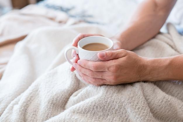 Warmte en energie in de ochtendkoffie. nieuwe gewoonte voor een dag. man in bed. handen rond witte kop latte.