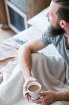 Warmte en energie in de ochtendkoffie. nieuwe gewoonte voor een dag. man in bed zijwaarts op zoek. handen rond witte kop latte.