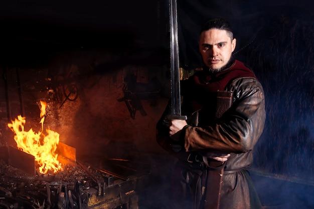 Warrior viking is dichtbij vuur in zijn smidse met wapens in handen.