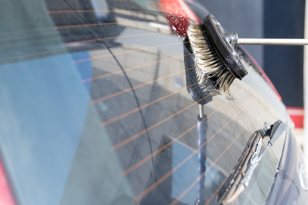 Was de achterruit van de auto met de hand met borstel en water met shampoo. self-service snelle wasstraat