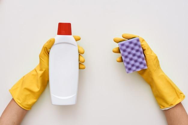 Was de kachel. reinigingsmiddel en spons in menselijke handen geïsoleerd