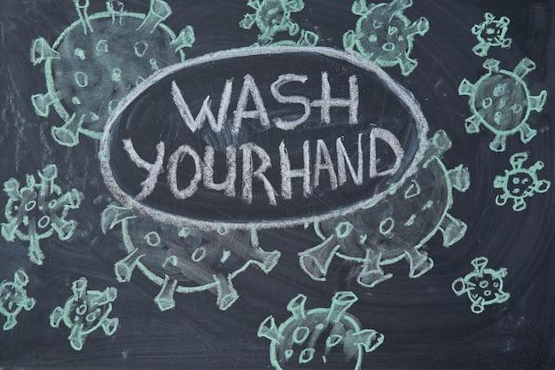 Was je hand. waarschuwing bij uitbraak. geschreven wit krijt op bord in verband met epidemisch coronavirus wereldwijd covid 19 pandemie tekst op zwarte achtergrond met vrije ruimte. getekende virusbacteriën