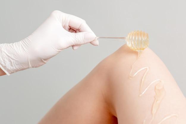 Was op honingsstok stroomt neer op vrouwelijk been in menselijke hand die beschermende handschoen draagt