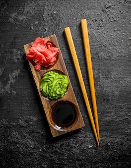 Wasabi, gemarineerde gember en sojasaus in een houten tribune met eetstokjes op zwarte rustieke lijst