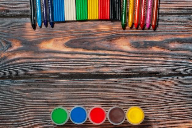 Waskleurpotloden, vingerverven en plasticine, copyspace, rustieke houten achtergrond