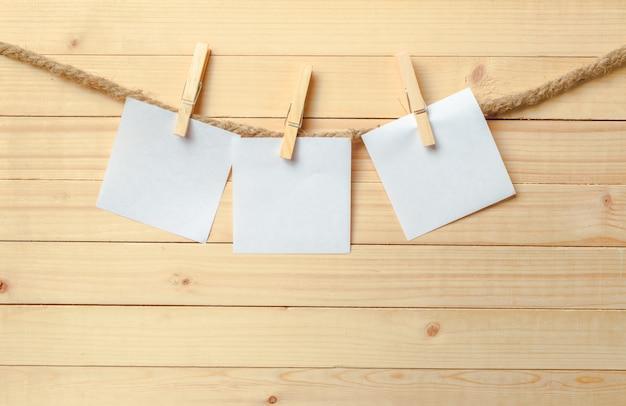 Wasknijper het hangen met leeg document op houten achtergrond
