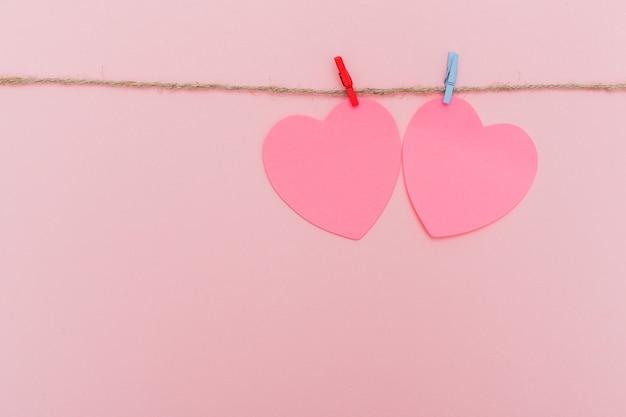 Wasknijpers en rode papieren harten op touw geïsoleerd op roze achtergrond