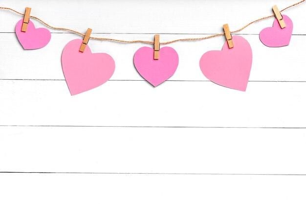 Wasknijpers met gekleurde harten die op kabel achter witte houten oppervlakte hangen. kopieer ruimte, bovenaanzicht.