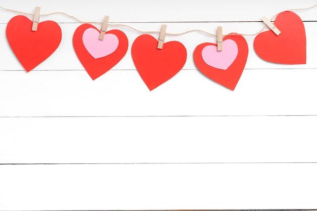 Wasknijpers met gekleurde harten die op kabel achter witte houten oppervlaktetafel hangen