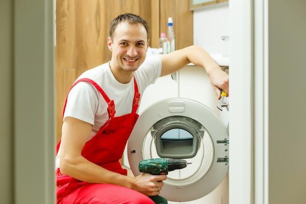 Wasmachine reparatie. reparateur handen met schroevendraaier demontage beschadigde eenheid voor reparatie