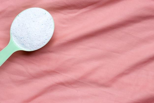 Wasmiddel poeder in maatlepel op roze doek. wasserij concept.