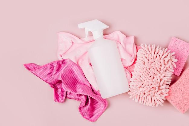 Wasmiddelen en reinigingsaccessoires in roze kleur. schoonmaak dienstverleningsconcept. plat leggen, bovenaanzicht.