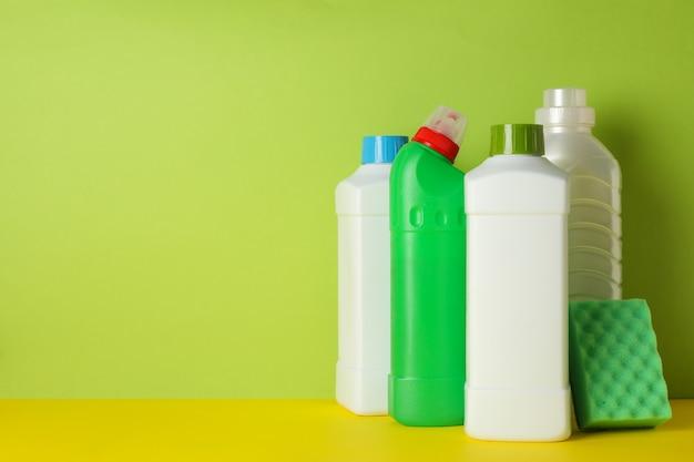 Wasmiddelen en spons op groene achtergrond, ruimte voor tekst