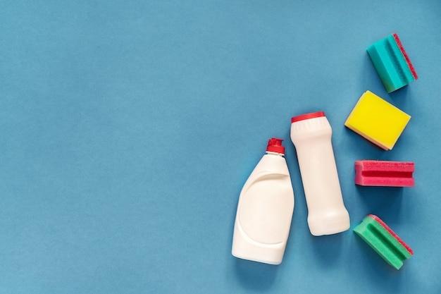 Wasmiddelen en sponzen geïsoleerd op blauw