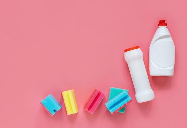 Wasmiddelen en sponzen geïsoleerd op roze
