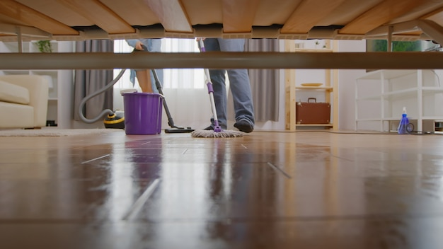 Wassen met een dweil in huis, uitzicht onder de bank