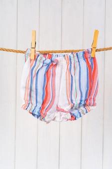 Wassen van babykleertjes die aan een touw zijn vastgemaakt om te drogen