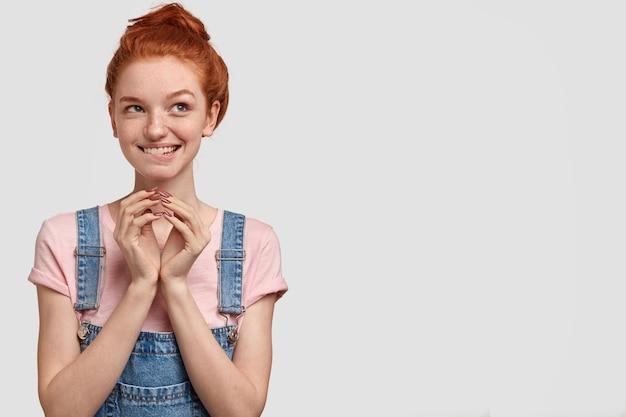 Wat als ik naar zijn huis kom? intrigerend positief sproeterig meisje houdt de handen bij elkaar, heeft een nieuwsgierige gezichtsuitdrukking, droomt over iets, bijt onderlip, staat over witte muur met lege ruimte